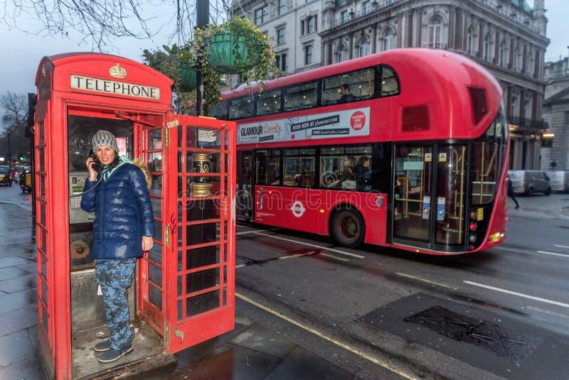 少妇谈话在电话在电话亭在伦敦 图库摄影