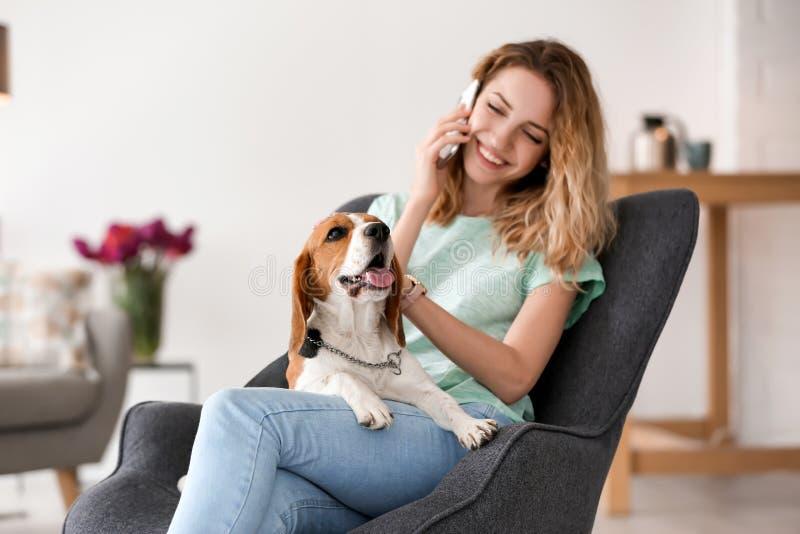 少妇谈话在电话,当抚摸她的狗时 免版税库存图片