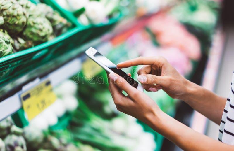 少妇购物购买健康食物在超级市场迷离背景中 使用在sto的智能手机关闭看法女孩购买产品 免版税库存照片