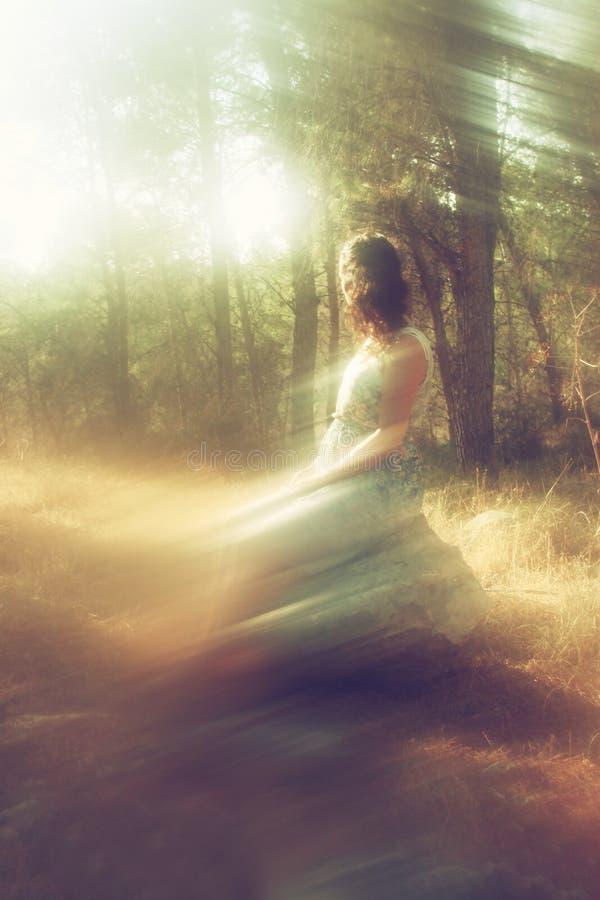 少妇超现实的被弄脏的背景坐石头在森林里 免版税库存照片