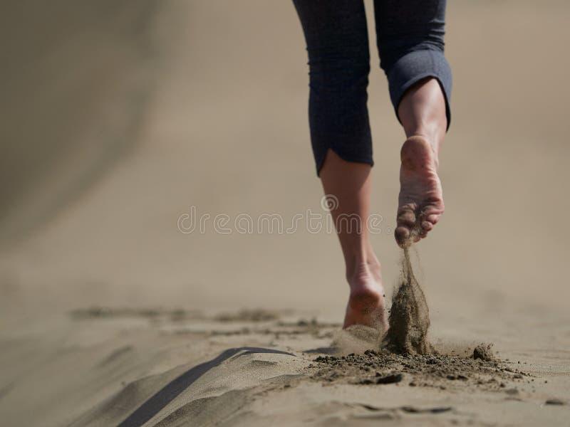 少妇跑步/走的赤脚在海滩的 免版税库存图片