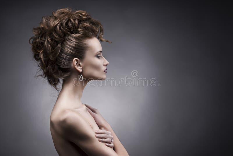 少妇边在灰色背景的秀丽画象 库存图片