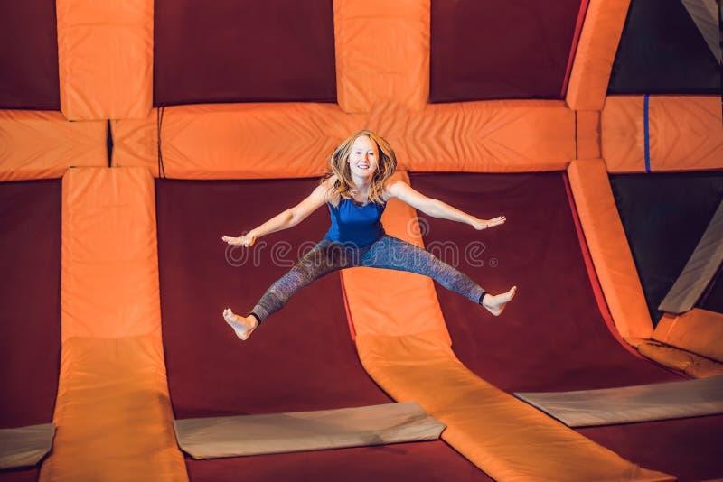 少妇运动员跳跃在一张绷床在健身的公园 免版税库存照片