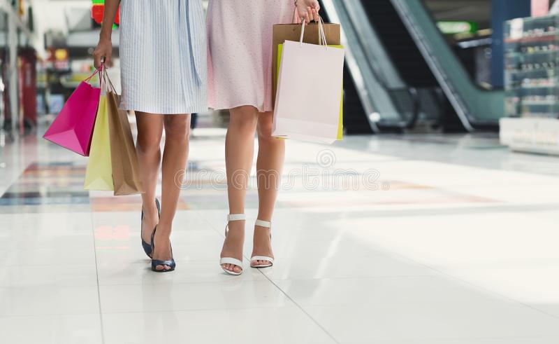 少妇运载的购物袋,当走在购物中心时 免版税库存照片