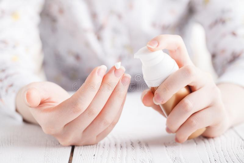 少妇递应用润湿的奶油于她的皮肤 库存图片