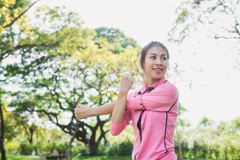 少妇通过舒展她的胳膊准备好行使和做瑜伽使她的身体兴奋在公园 免版税库存照片