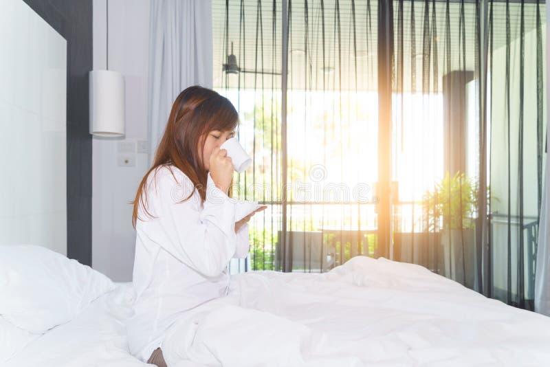少妇醒了和饮用的咖啡或茶在床上在sunl下 库存图片