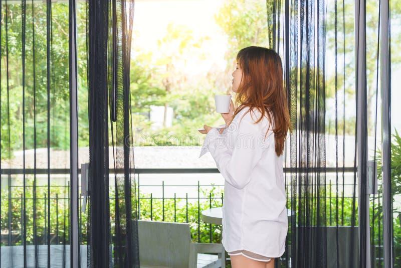 少妇醒了和饮用的咖啡或茶在阳光下 g 图库摄影
