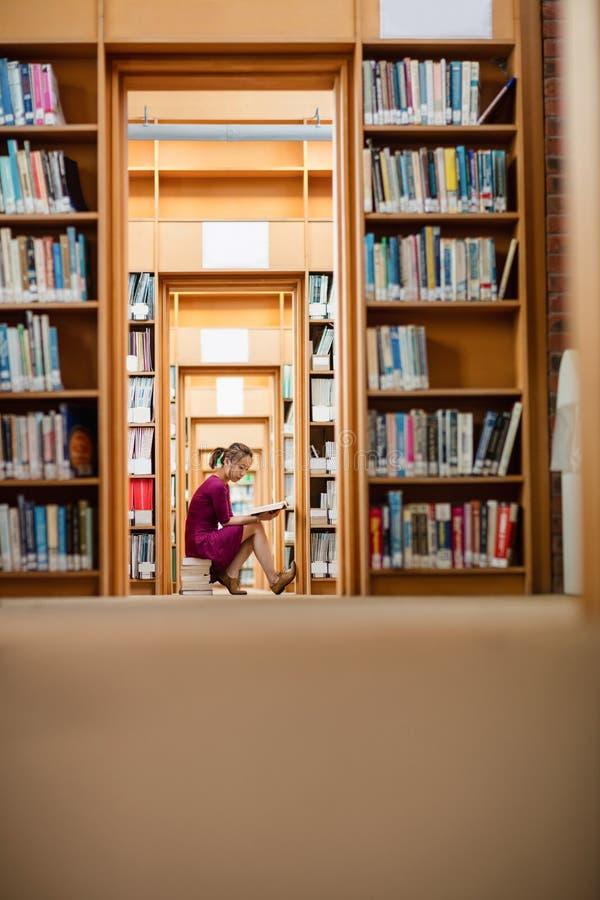 少妇阅读书在图书馆里 免版税图库摄影
