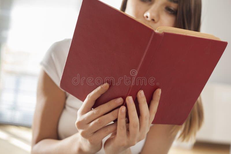 少妇阅读书在家 免版税库存图片