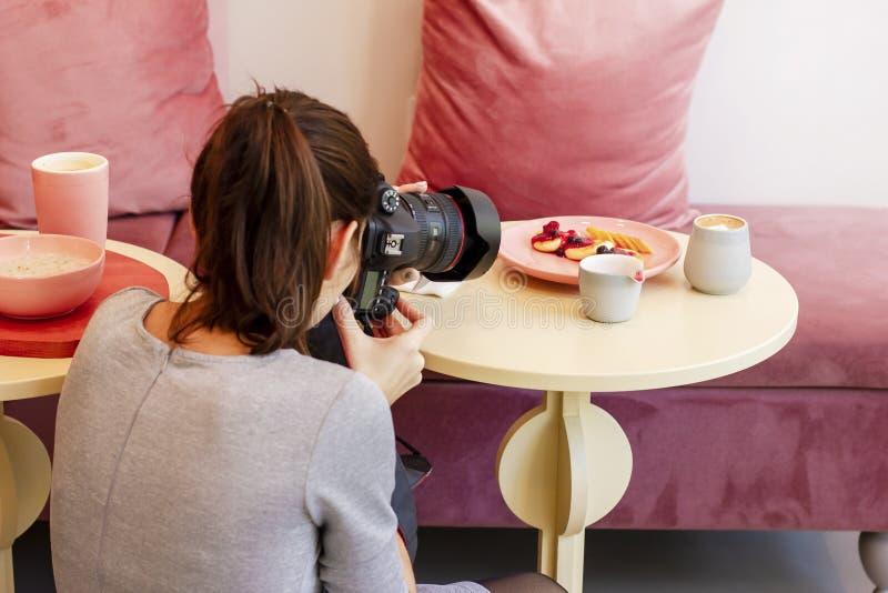 少妇食物摄影师博客作者射击在咖啡馆的早餐 库存图片