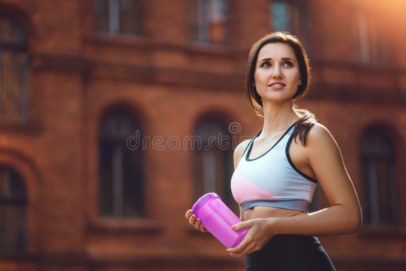 少妇饮用的体育补充在跑或行使以后室外 库存图片