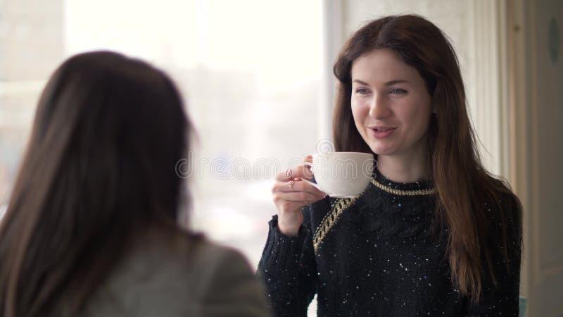 少妇饮用的咖啡和谈话与朋友在会议期间在咖啡馆 免版税库存图片