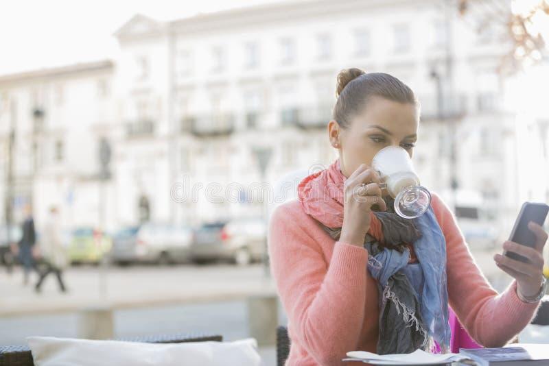 少妇饮用的咖啡,当使用手机在边路咖啡馆时 免版税图库摄影