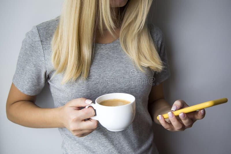 少妇饮用的咖啡witn使用智能手机的其他手 库存图片