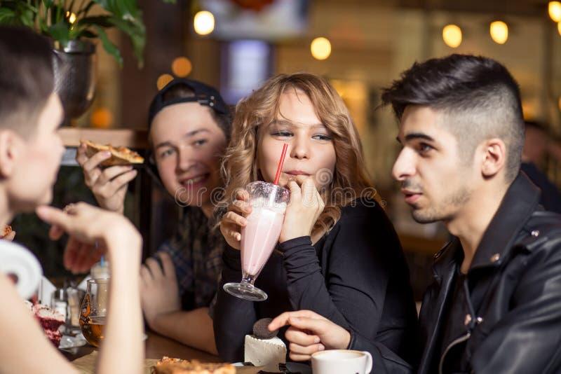 少妇饮用的奶昔,当坐与朋友在咖啡馆时 免版税库存照片