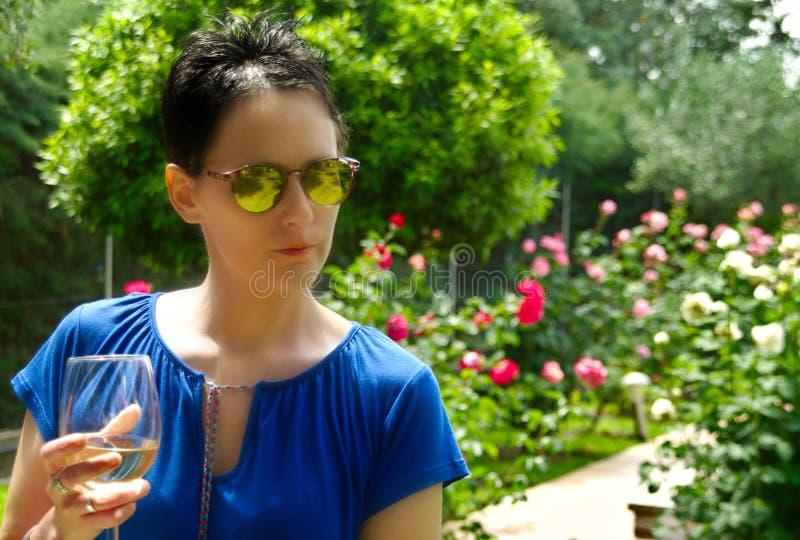 少妇饮用的白葡萄酒在庭院里 免版税库存照片