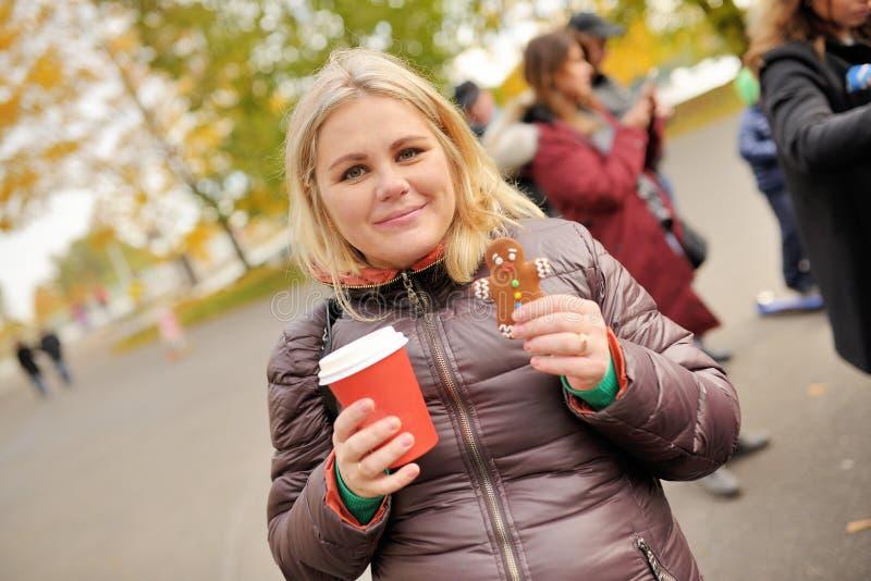 少妇饮用的coffe用在秋天时间的姜姜饼在公园 库存图片