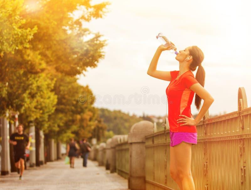 少妇饮用水在跑以后在城市 库存图片