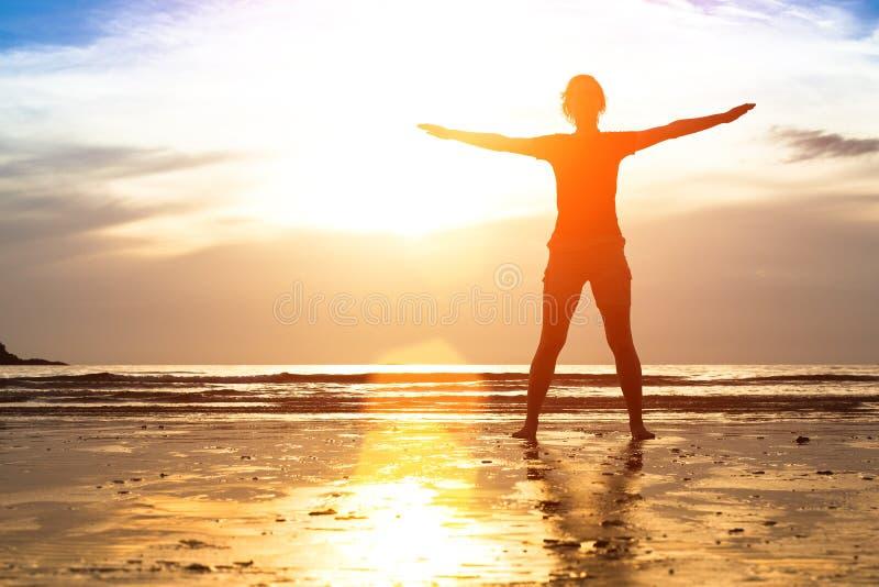 少妇,在海滩的锻炼在日落 图库摄影