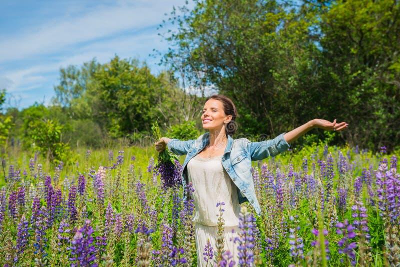 少妇,愉快,在紫罗兰色羽扇豆中的领域的身分,微笑,紫色花 在背景的蓝天 夏天,与 免版税库存照片