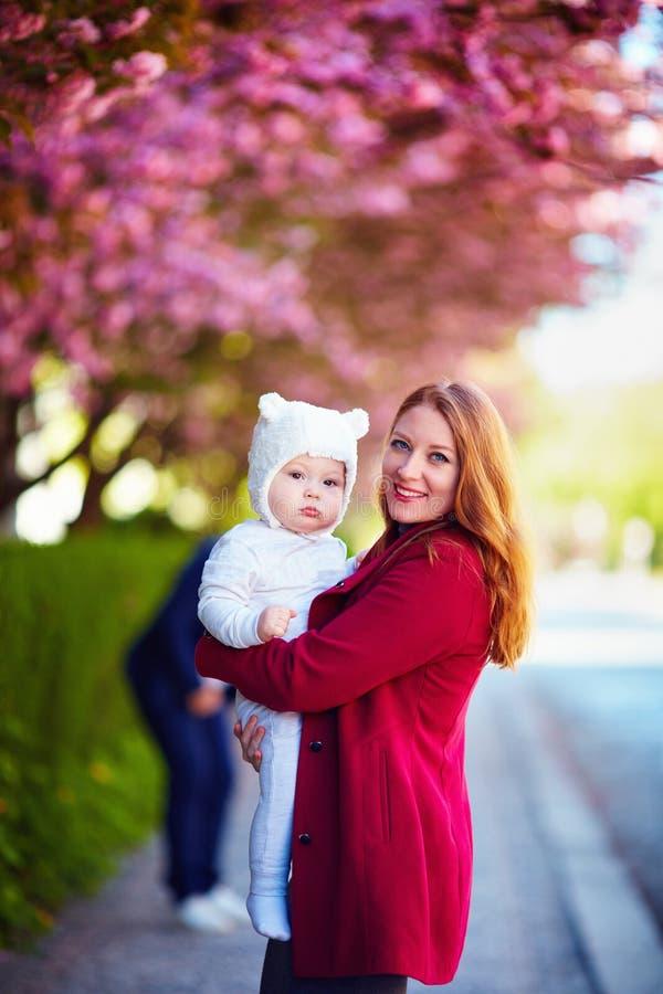 少妇,有逗人喜爱的婴儿婴孩的愉快的母亲画象胳膊的,在步行在春天城市 免版税库存图片
