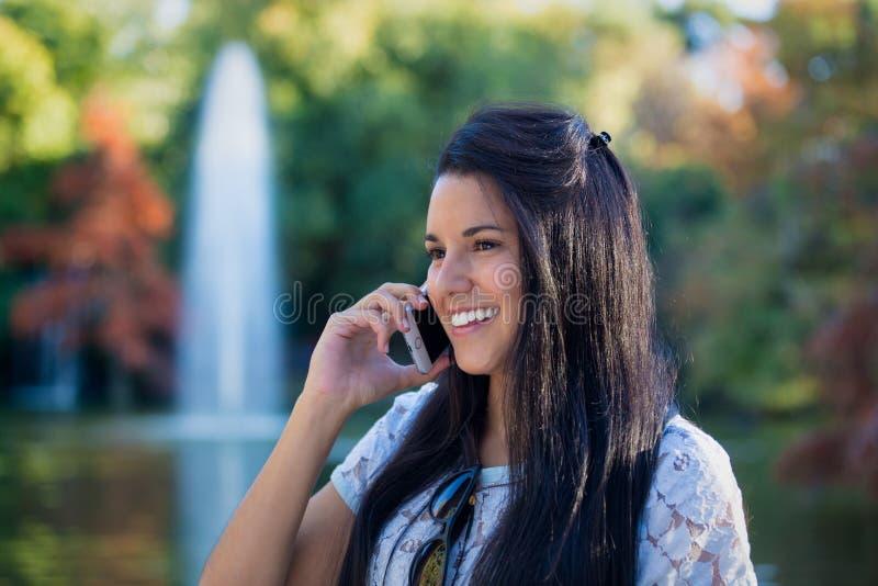 少妇说在电话里在公园 库存图片
