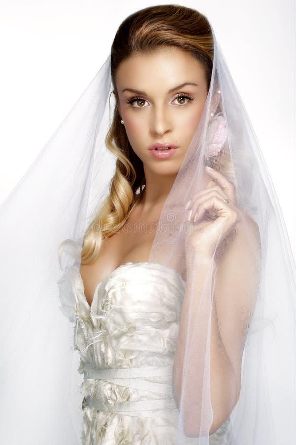 少妇画象摆在与白色brid的婚礼礼服的 免版税库存照片