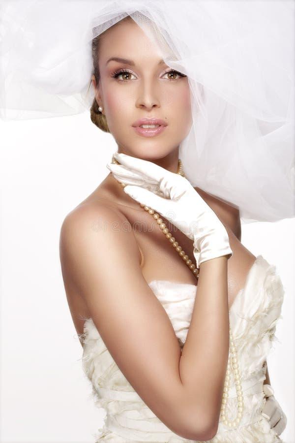 少妇画象摆在与白色brid的婚礼礼服的 免版税图库摄影