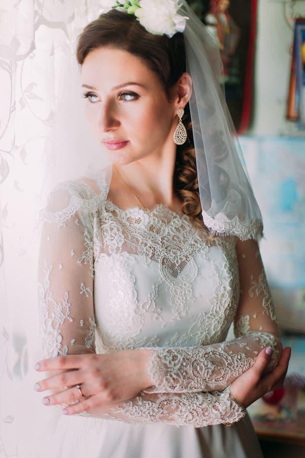 少妇画象有别致的厚实的头发的,看往窗口的佩带的白色礼服,在外形 免版税库存照片