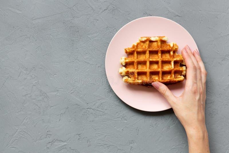 少妇` s手采取一个传统比利时华夫饼干,顶上的看法 从上,顶上 具体背景 免版税图库摄影