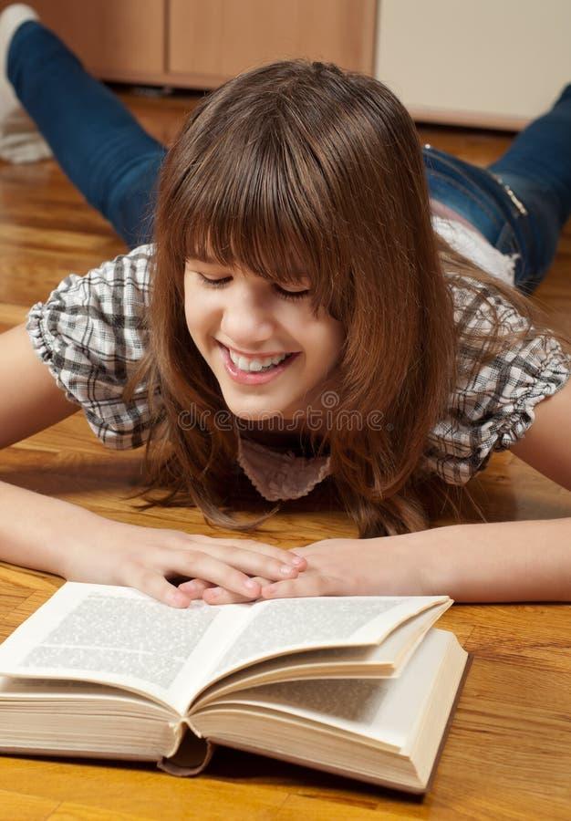 少年书女孩愉快的读取 免版税库存图片