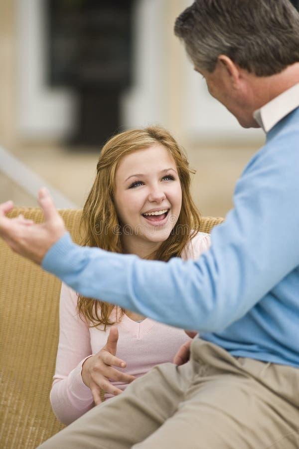 少年交谈的女儿的父亲 库存图片