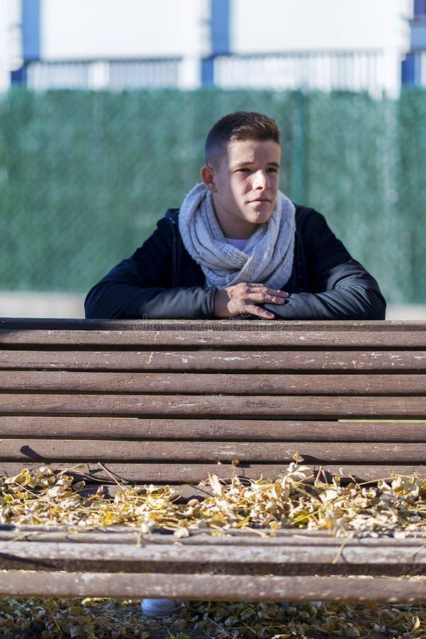 少年人放松在庭院长木凳的姿势 库存图片