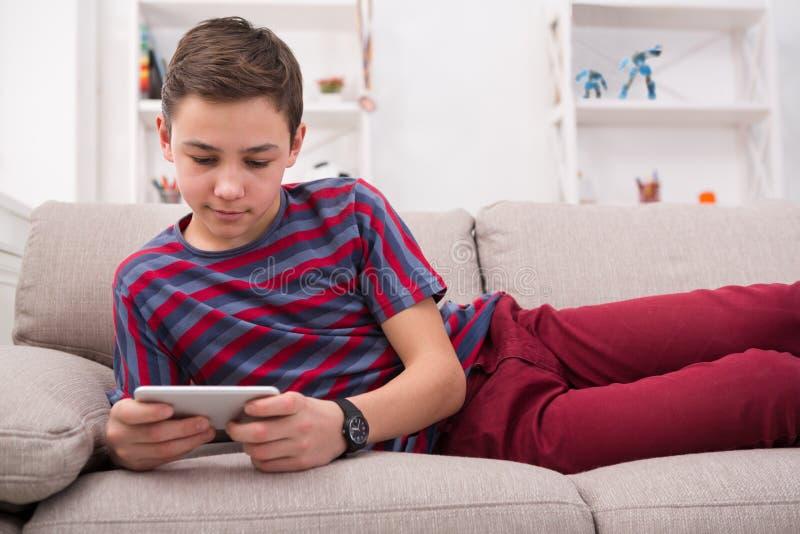 少年传讯在家在网上在智能手机在客厅 库存图片