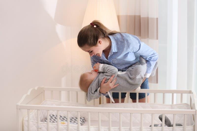 少年保姆把可爱的小婴儿放在婴儿床 白天睡眠 图库摄影