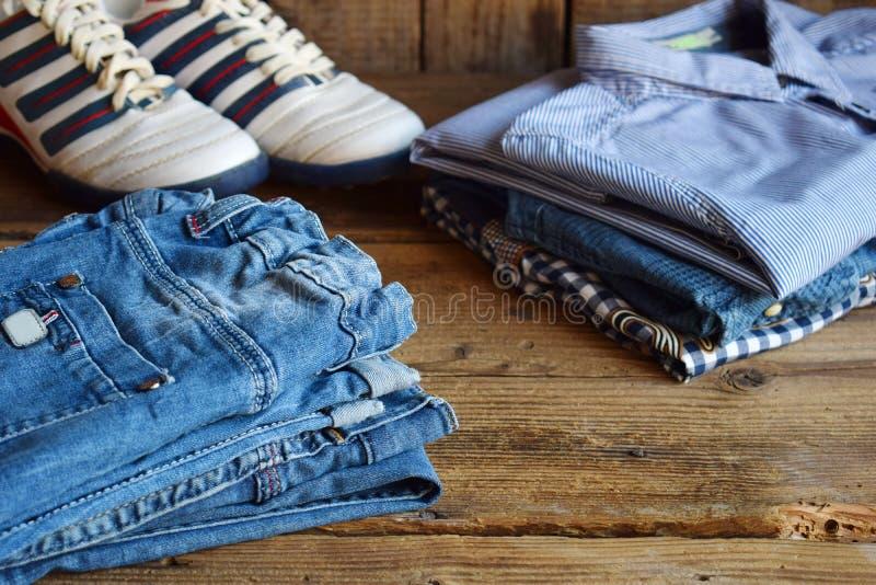 少年偶然成套装备 男孩鞋子、衣物和辅助部件在木背景-毛线衣,衬衣,长裤,牛仔裤,运动鞋 顶层 库存图片