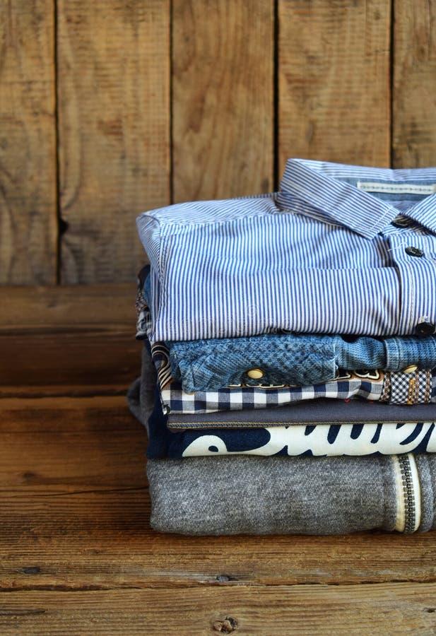 少年偶然成套装备 男孩鞋子、衣物和辅助部件在木背景-毛线衣,衬衣 顶视图 平的位置 库存照片