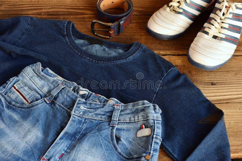 少年偶然成套装备 男孩鞋子、衣物和辅助部件在木背景-毛线衣,长裤,运动鞋 顶视图 平面 免版税库存照片