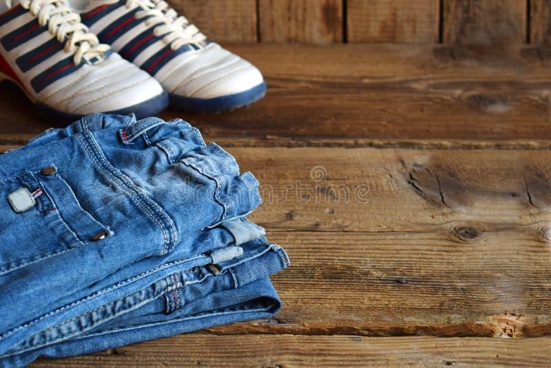 少年偶然成套装备 男孩鞋子、衣物和辅助部件在木背景-牛仔裤,运动鞋 顶视图 平的位置 免版税库存图片