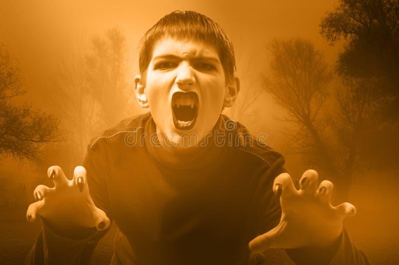 少年吸血鬼在有薄雾的森林里 库存照片