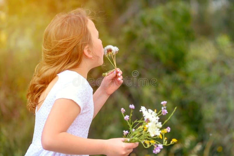少年女孩吹的蒲公英 免版税库存图片