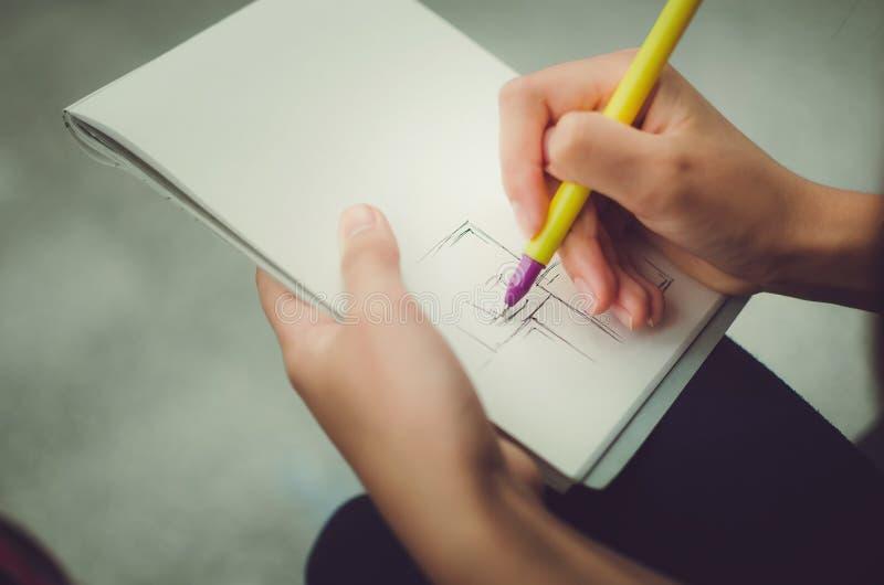 少年女孩画在笔记本的一支笔 免版税库存图片