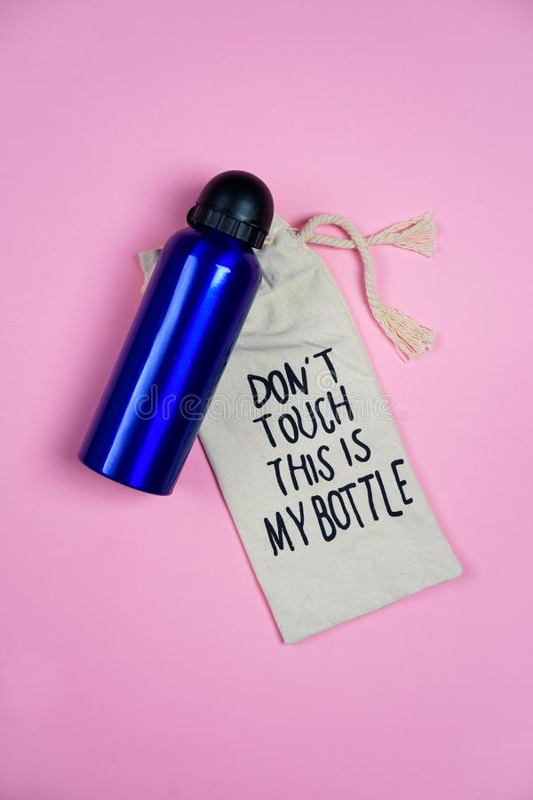 少年女孩集合蓝色瓶与在` t接触此的唐上写字的水和组织袋子是我的在浅粉红色的背景的瓶 免版税库存照片