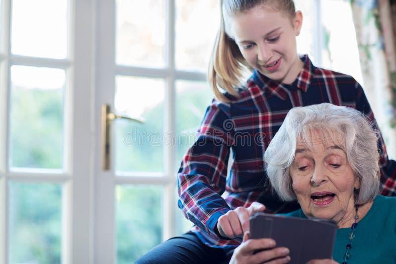 少年孙女显示祖母如何使用数字式选项 免版税库存照片