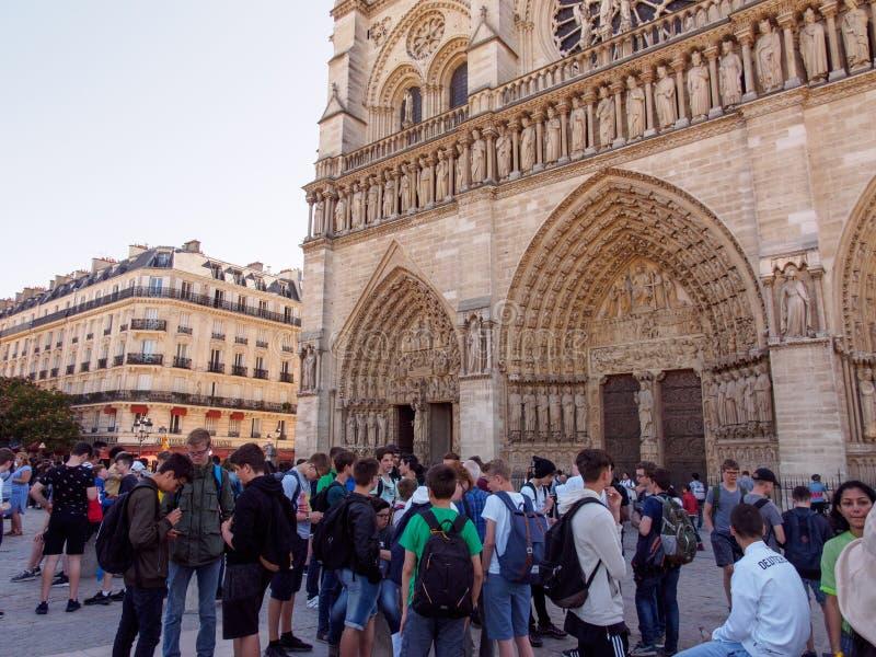 少年学生在Notre Dame,巴黎,法国前面等待 免版税库存照片