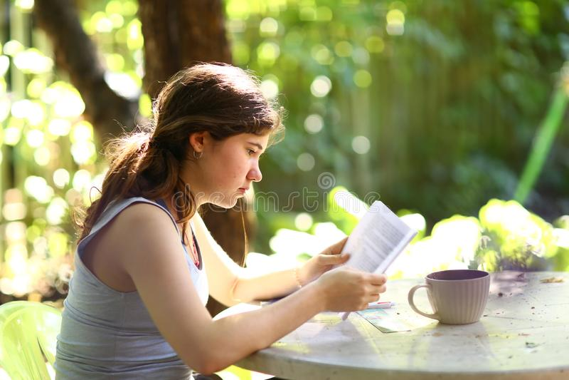 少年学生女孩与茶杯的阅读书 免版税库存图片