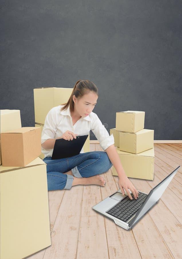 少年所有者在家与剪贴板,网上购物的膝上型计算机一起使用写命令的女商人 免版税库存图片
