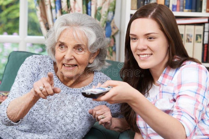少年有祖母的孙女观看的电视 免版税库存照片