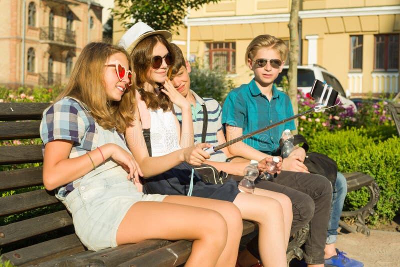 少年朋友女孩和男孩坐长凳在城市,谈话,看在电话,做selfie照片 免版税库存图片